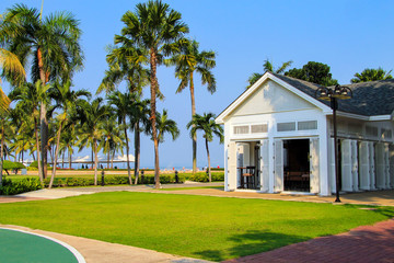 White wooden open pavilion in Thailand resort among green palm trees and lawns. Wooden house exterior