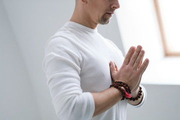 A man in white clothes on a white background with his hands folded on his chest. Meditation and prayer, yoga.