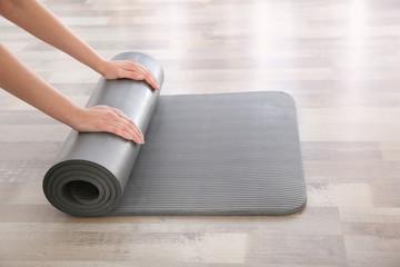Foto op Textielframe School de yoga Woman rolling yoga mat on floor indoors, closeup