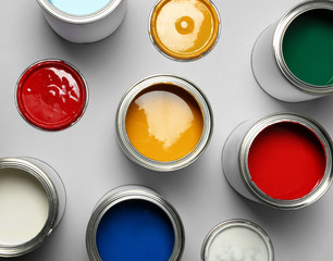 Open paint cans on grey background, top view