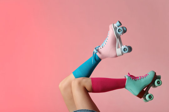 Woman with vintage roller skates on color background, closeup. Space for text