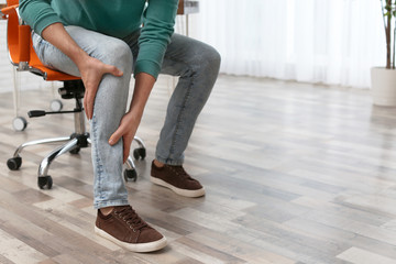 Man suffering from leg pain indoors, closeup with space for text