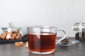 Cup of hot tea on table against blurred background