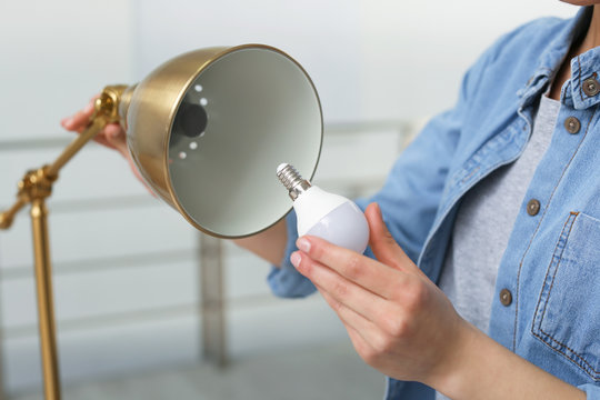 Woman changing light bulb in lamp indoors, closeup