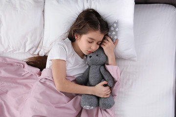 Beautiful little girl with toy rabbit sleeping in bed, top view