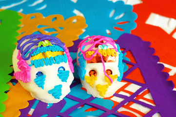 couple of sugar skulls on orange yellow purple green and blue perforated paper