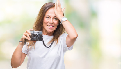 Middle age hispanic woman taking pictures using vintage photo camera over isolated background stressed with hand on head, shocked with shame and surprise face, angry and frustrated.