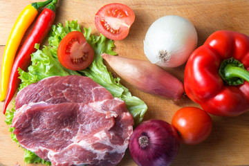Pork-neck meat steaks on lettuce on background of radishes, tomato, red chili peppers, yellow chili peppers, green paprika, yellow paprika, red paprika, black pepper. Horizontal. Red onions, shallots