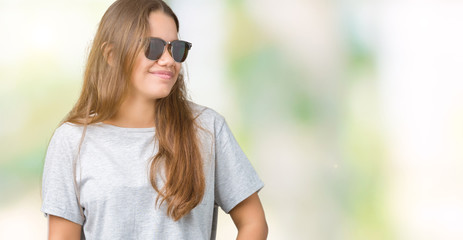 Young beautiful brunette woman wearing sunglasses over isolated background looking away to side with smile on face, natural expression. Laughing confident.