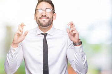 Young handsome business man wearing glasses over isolated background smiling crossing fingers with hope and eyes closed. Luck and superstitious concept.
