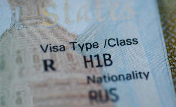 Fragment of H1B visa (for specialty workers) stamp in passport, blurred april calendar on background. H1B visa program deadline concept. Close up view.