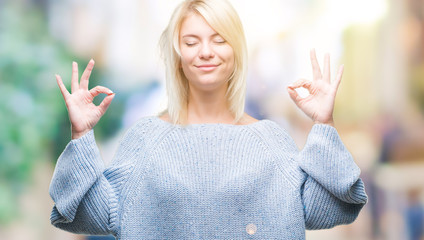 Young beautiful blonde woman wearing winter sweater over isolated background relax and smiling with eyes closed doing meditation gesture with fingers. Yoga concept.