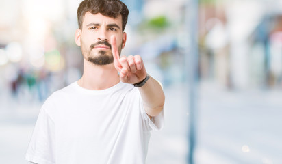 Young handsome man wearing white t-shirt over isolated background Pointing with finger up and angry expression