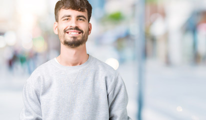 Young handsome man wearing sweatshirt over isolated background Hands together and fingers crossed smiling relaxed and cheerful. Success and optimistic