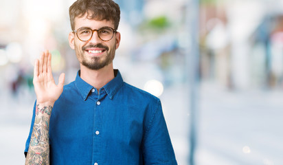 Young handsome man wearing glasses over isolated background Waiving saying hello happy and smiling, friendly welcome gesture