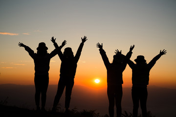 Silhouette of young woman are standing on top of the mountain with raised hands relaxing with sunrise by nature at sunrise, Life style, Group of happy at sunrise or sunset, First morning light
