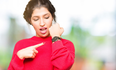 Young beautiful woman wearing red sweater and bun In hurry pointing to watch time, impatience, upset and angry for deadline delay
