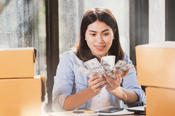 Asia woman holding us dollar banknotes money smiles with happy.