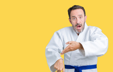 Handsome middle age senior man wearing kimono uniform over isolated background In hurry pointing to watch time, impatience, upset and angry for deadline delay