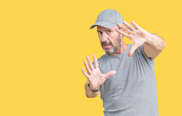Handsome middle age hoary senior man wearing sport cap over isolated background Smiling doing frame using hands palms and fingers, camera perspective
