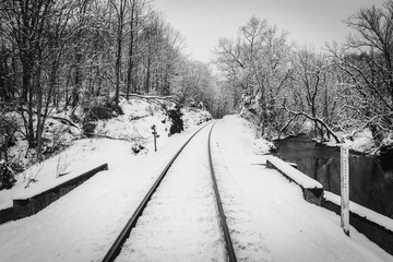 A snow covered railroad track and creek in rural Carroll County, Maryland.