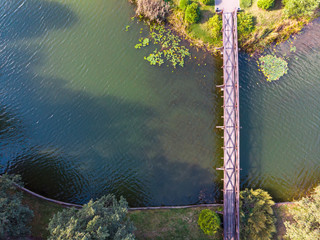 aerial top view of wooden bridge over blue water pond connecting two islands, reflections in water