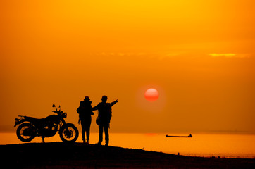Silhouette Couple with a motorbike at river side at sunset.