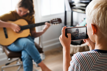 Brother recording his sister playing the guitar