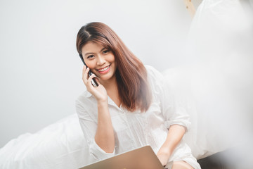 Beautiful Asian woman using laptop and smart phone in bed room for online shopping, Asian woman lifestyle concept