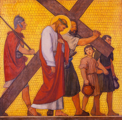 Wall Mural - PRAGUE, CZECH REPUBLIC - OCTOBER 17, 2018: The painting Simon of Cyrene helps Jesus carry the cross in the church kostel Svatého Cyrila Metodeje by  S. G. Rudl (1935).