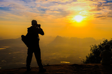 Man backpacker with her dslr camera silhouette in sunset background