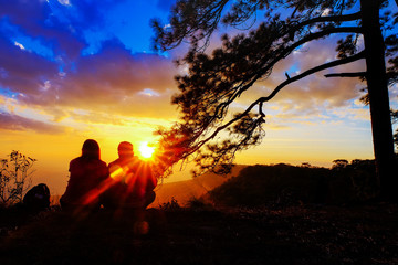 Silhouette of happy young couple in love looking view sunset on the mountain. Romantic couple in love