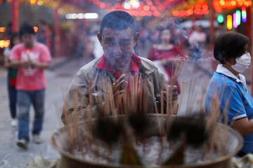 A man lights incense while praying in a Chinese temple ahead of Lunar New Year in Chinatown in Bangkok