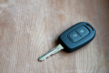 Black car key with with wireless remote control and lock unlock button signs on brown wooden background with copy space for text.