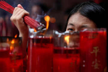 Woman lights incense sticks as she prays during celebrations of the Chinese Lunar New Year of the Pig at a temple in Jakarta