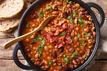 American cowboy beans with ground beef, bacon in a spicy sauce close-up. horizontal top view