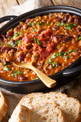 American cowboy beans with ground beef, bacon in a spicy sauce close-up. vertical