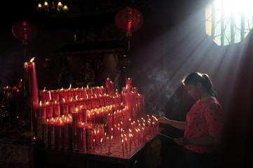 Woman lights candles as she prays during celebrations of the Chinese Lunar New Year at a temple in Jambi