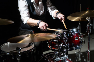 Drummer with a drumsticks in his hands playing on drum set on stage on the black background