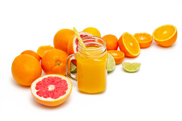 Freshly blended yellow and orange fruit smoothie in glass jar. Glass jar mugs with orange health smoothie, lime, grapefruit, lemon, tangerine. Selective focus. Copy space. Vegetarian food concept.