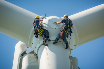 Inspection engineers preparing to rappel down a rotor blade of a wind turbine in a North German wind farm on a clear day with blue sky. Wall mural