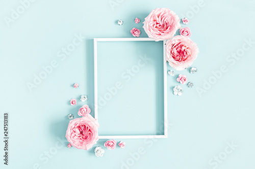 Flowers composition. Photo frame, rose flowers on pastel blue background. Valentines day, mothers day, womens day, spring concept. Flat lay, top view, copy space