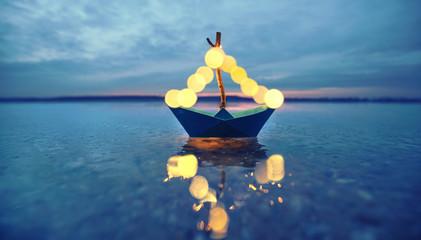 romantischer Abend - leuchtendes Boot am Strand
