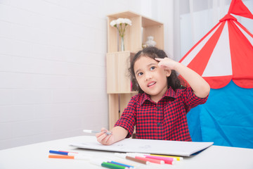 Little asian girl thinking and drawing picture on table at home