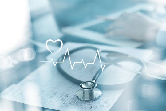 Stethoscope with heart beat report and doctor analyzing checkup on laptop in health medical laboratory background.