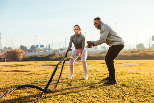 Personal trainer training a girl with ropes