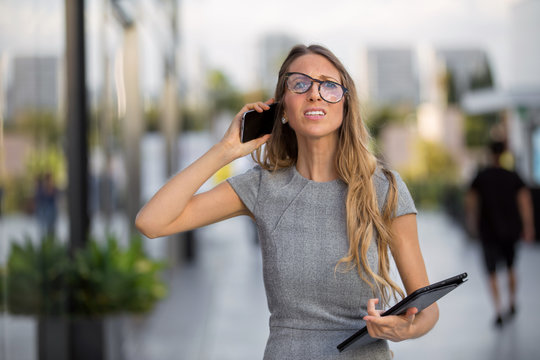 Stressed business person struggling to use cellphone, bad reception, poor service, weak signal