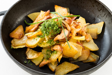 Tasty unhealthy food. Fried potato garnished with dill. Full skillet close up.