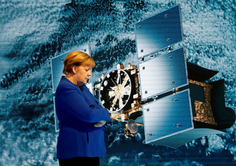 German Chancellor Angela Merkel stands in front of a large screen introducing NEC's satellite-mounted radar system for monitoring urban infrastructure and disaster prevention as she visits NEC Future Creation Hub at the headquarters of NEC in Tokyo