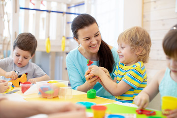 Tutor teaches children handcraft in kindergarten or playschool